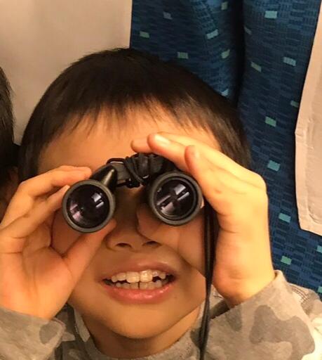 双眼鏡でトンネルのライトを眺めようとするコドモ